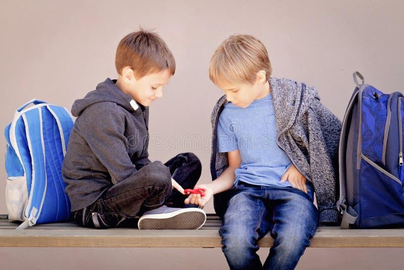 Grundschulausbildung, Schule, Freundschaftskonzept - zwei Jungen mit den Rucksäcken, die mit Spinner sitzen, sprechen und spielen lizenzfreie stockfotos