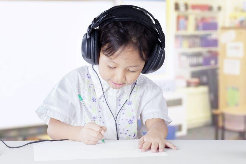 Grundschulestudent, der in der Klasse mit Kopfhörer studiert lizenzfreie stockbilder