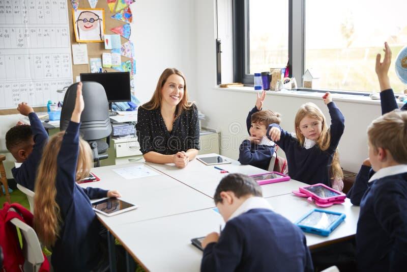 Grundskola för barn mellan 5 och 11 årbarn som sitter på en tabell i ett klassrum med deras lärarinna som lyfter deras händer fotografering för bildbyråer