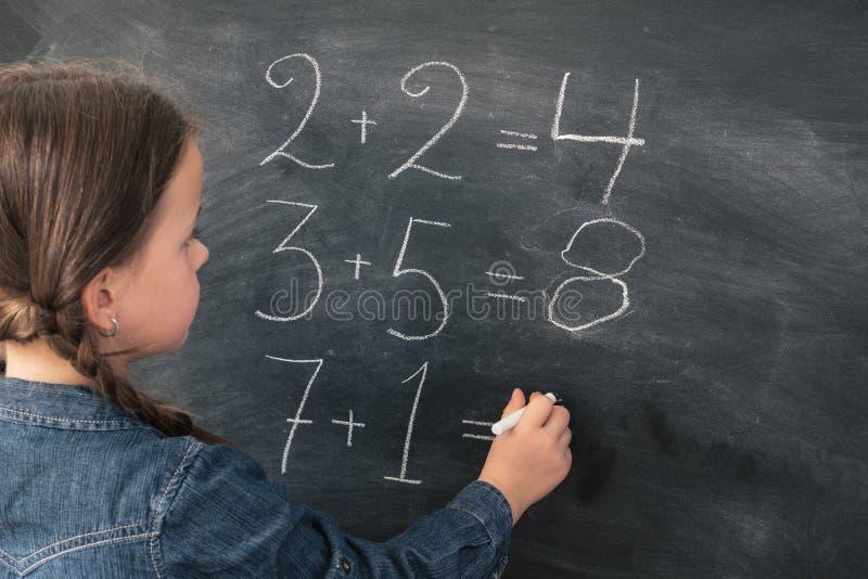 Grundskola för barn mellan 5 och 11 årflicka att göra summamatematikgrupp royaltyfria foton