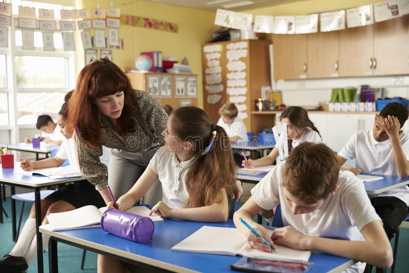 Grundskola för barn mellan 5 och 11 årläraren hjälper en elev på skrivbordet med classwork royaltyfri foto