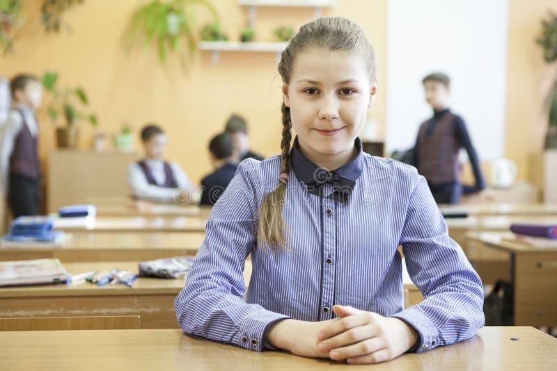 Grundskola för barn mellan 5 och 11 årstudent som sitter på tabellen i klassrumet på fördjupningstid, stående av den preteen flic arkivfoto