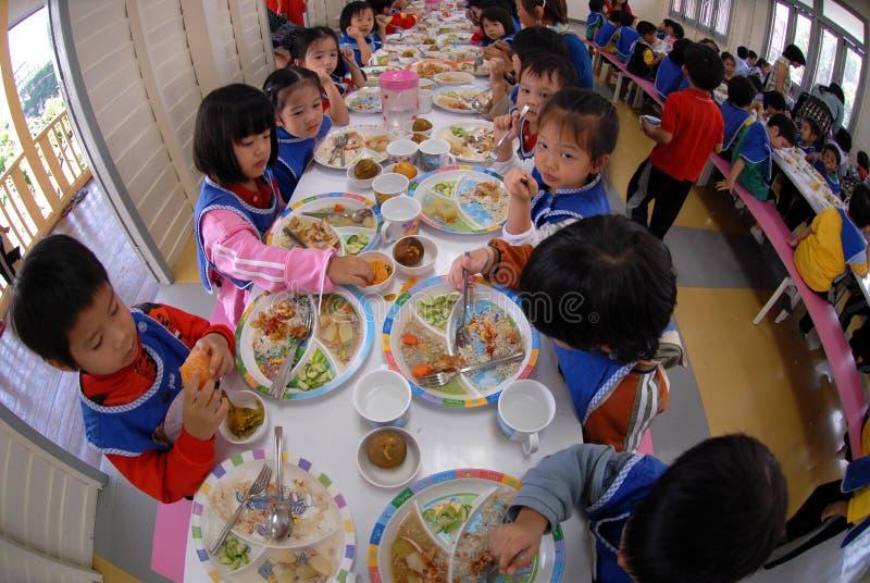 Grundskola för barn mellan 5 och 11 årstudenter äter lunch i skolakantin arkivfoto