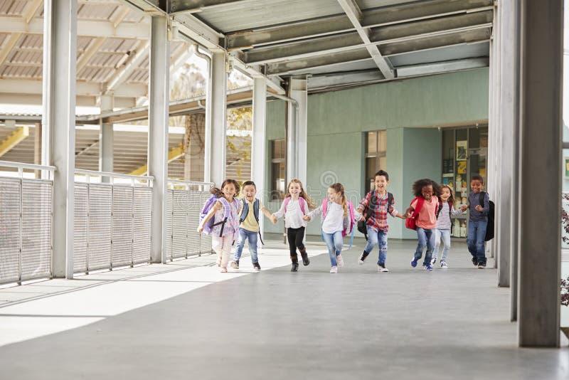 Grundskola för barn mellan 5 och 11 årungar kör innehavhänder i skolakorridor royaltyfri bild