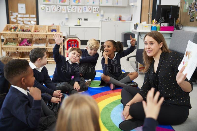 Grundskola för barn mellan 5 och 11 årungar som sitter på golvet i ett klassrum med deras lärare som lyfter händer för att svara  royaltyfri bild