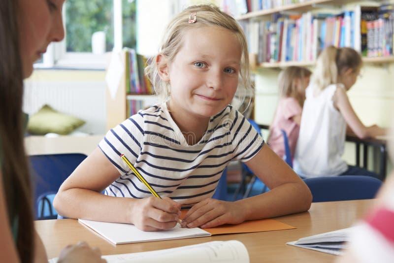 Grundskolaelev som arbetar på skrivbordet i klassrum royaltyfri fotografi