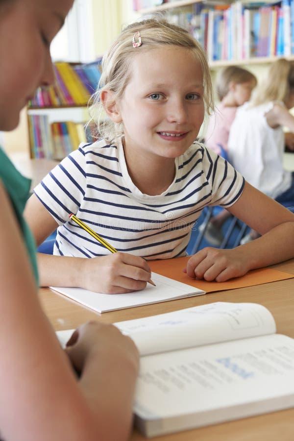 Grundskolaelev som arbetar på skrivbordet i klassrum arkivbild
