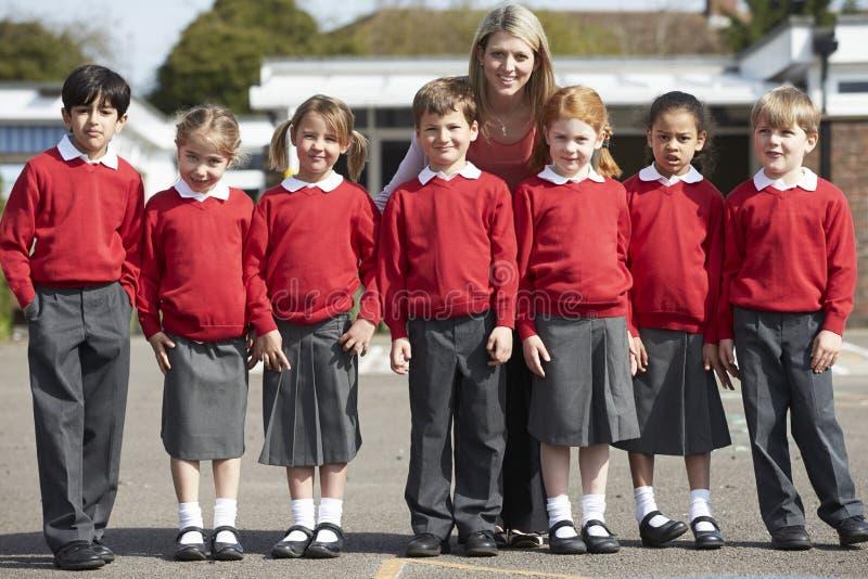 Grundskolaelever med läraren In Playground royaltyfria foton