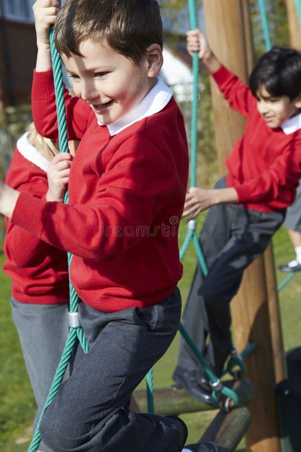 Grundskolaelever på klättringutrustning royaltyfri bild