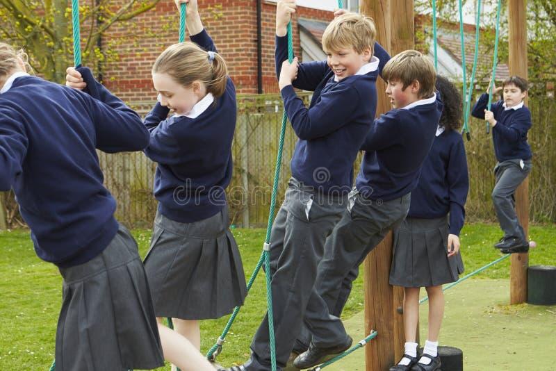 Grundskolaelever på klättringutrustning royaltyfri foto