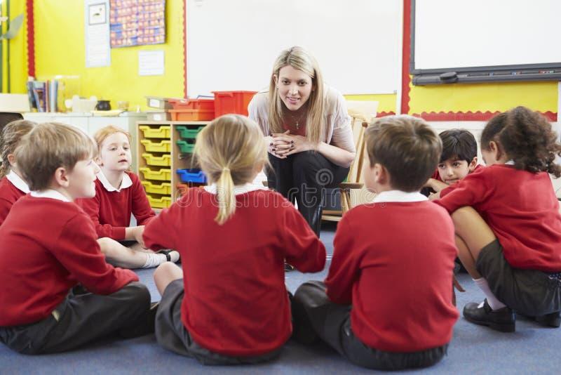 Grundskolaelever som berättar berättelse till läraren arkivfoton