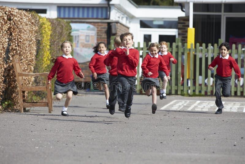 Grundskolaelever som kör i lekplats royaltyfria bilder