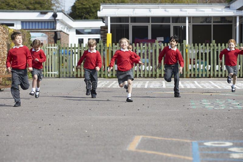 Grundskolaelever som kör i lekplats arkivfoto