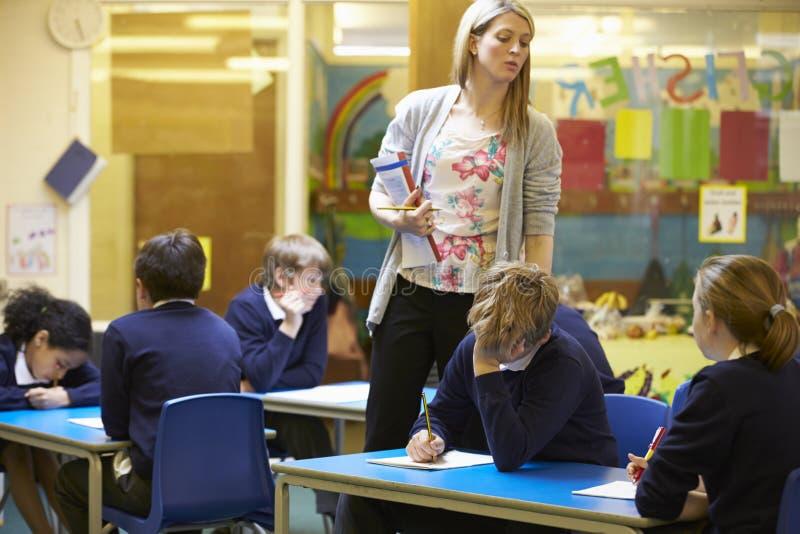 Grundskolaelever som sitter undersökning i klassrum arkivfoto