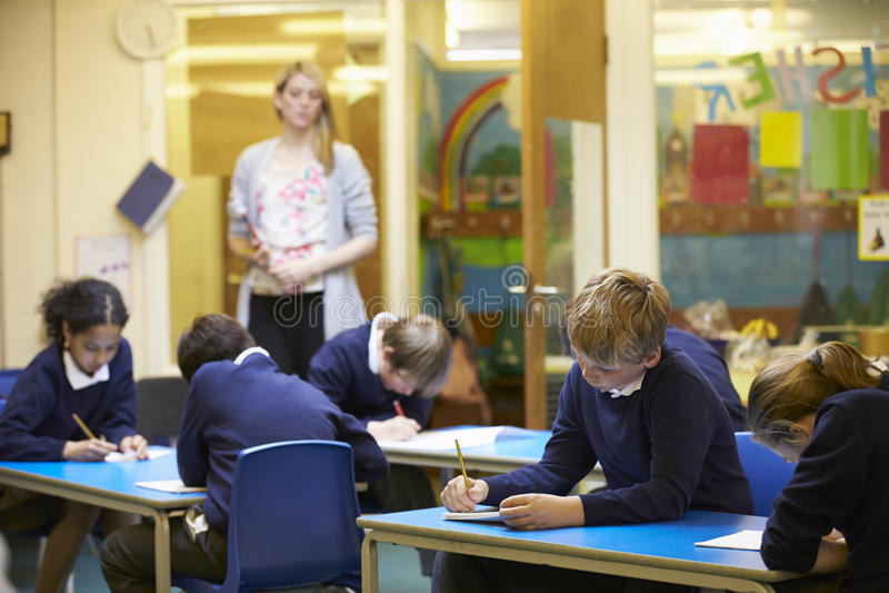 Grundskolaelever som sitter undersökning i klassrum arkivbilder