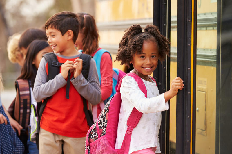 Grundskolaflicka på framdelen av skolbussköen arkivfoton