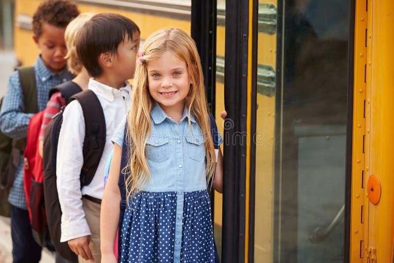 Grundskolaflicka på framdelen av skolbussköen royaltyfri foto