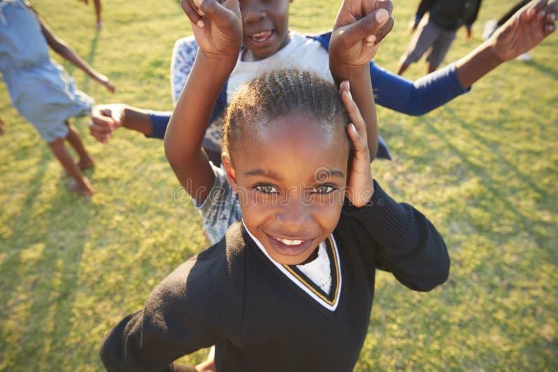 Grundskolaflicka som utomhus poserar till kameran, hög vinkel royaltyfri bild