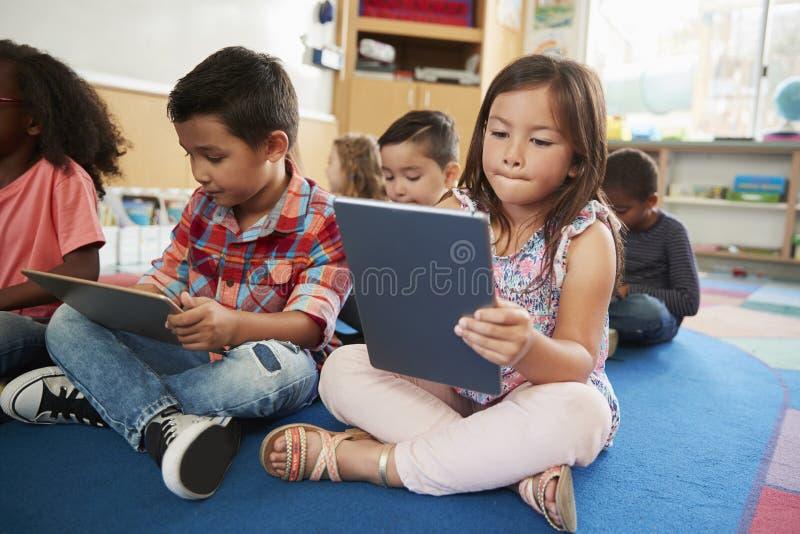 Grundskolagrupp som använder upp minnestavladatorer, slut royaltyfri bild