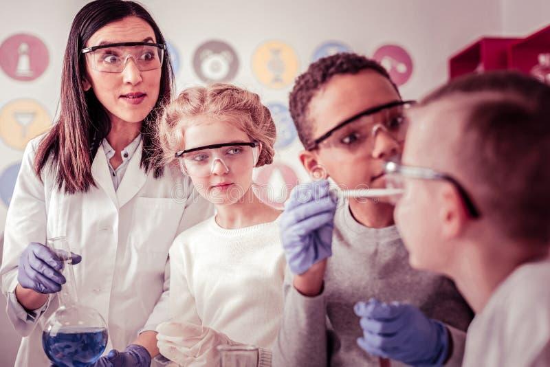 Grundskolagrupp som ser förvånad på deras klasskompis arkivbilder