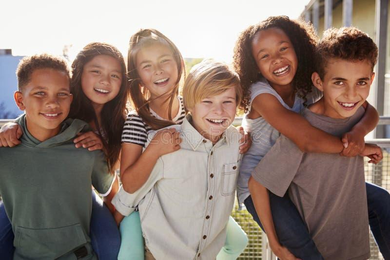Grundskolan lurar att le till kameran på avbrottstid royaltyfria bilder