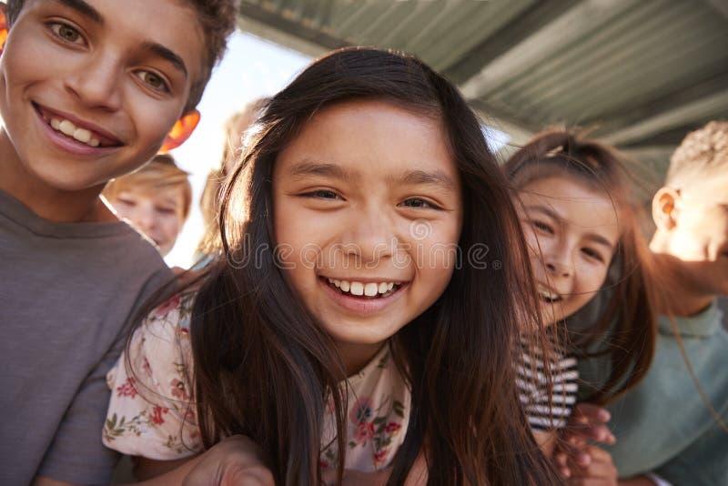 Grundskolan lurar att le till kameran, slut upp royaltyfri foto