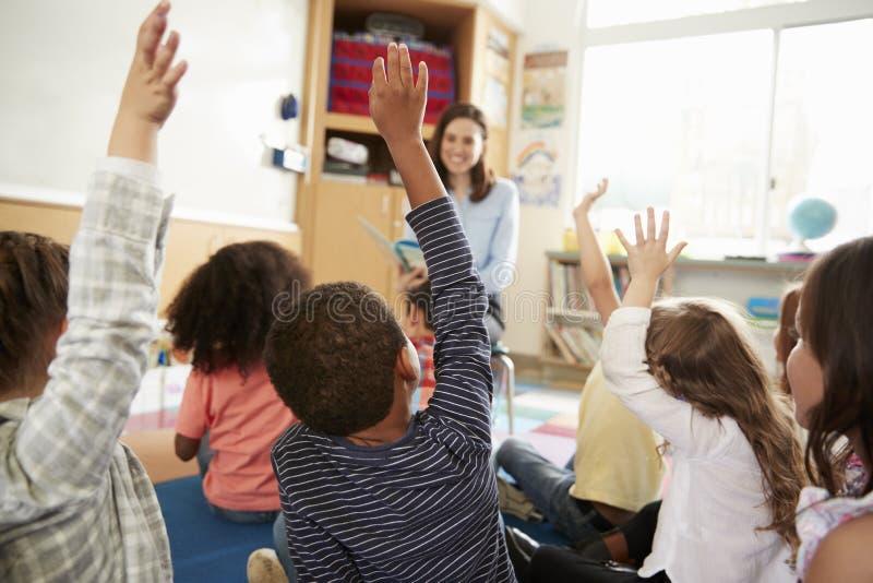 Grundskolan lurar att lyfta händer till läraren, baksidasikt royaltyfri foto