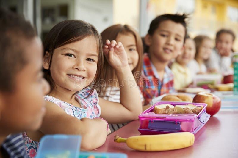 Grundskolan lurar att sitta en tabell med matsäckar royaltyfri foto