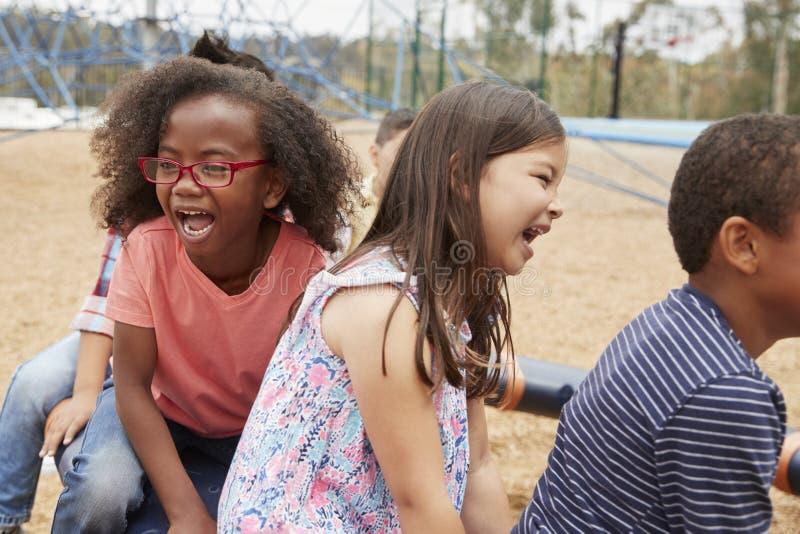 Grundskolan lurar att spela i lekplats, slut upp arkivbild