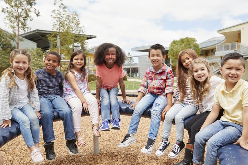 Grundskolan lurar sammanträde på karusell i schoolyarden royaltyfria bilder
