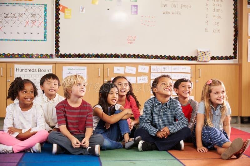 Grundskolan lurar sammanträde på klassrumgolv arkivbilder