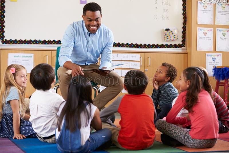 Grundskolan lurar sammanträde runt om lärare i ett klassrum royaltyfri foto