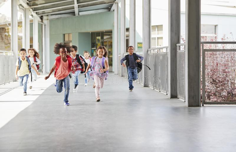Grundskolan lurar spring till kameran i skolakorridor arkivbild