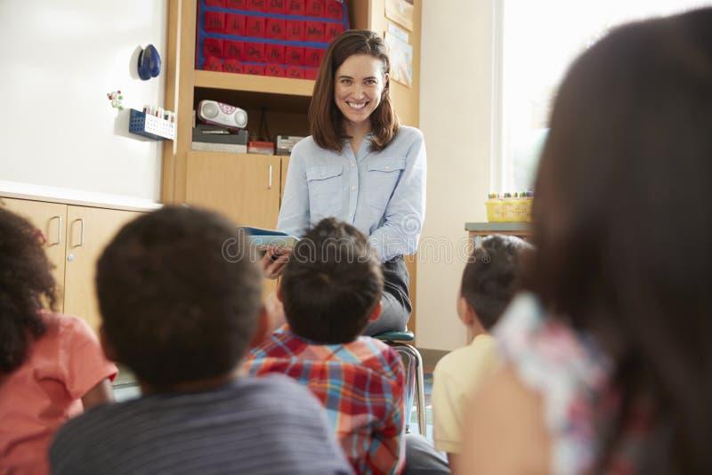Grundskolaungar lyssnar till läraren, baksidasiktsslut upp arkivbilder