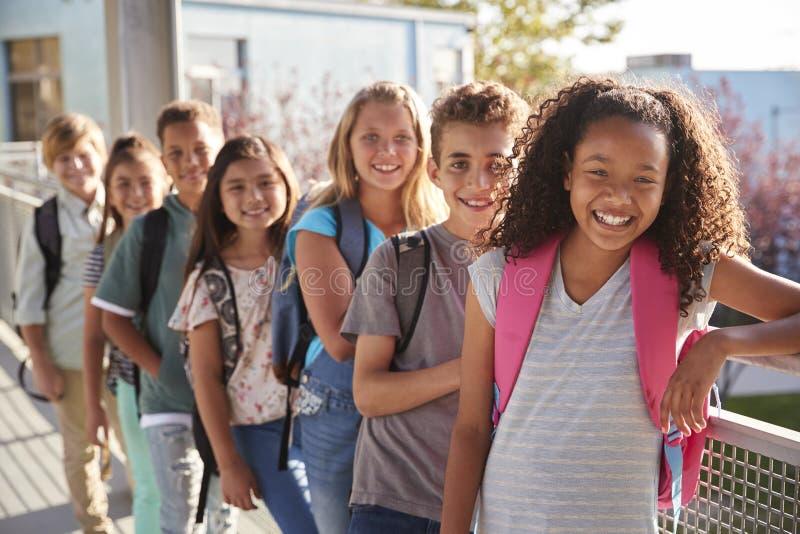 Grundskolaungar med ryggsäckar som ler på kameran arkivfoton