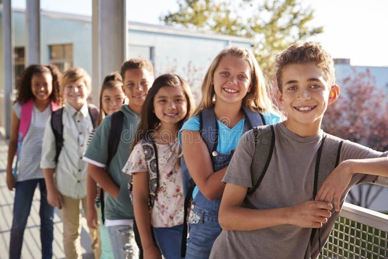 Grundskolaungar med ryggsäckar som ler till kameran arkivfoton