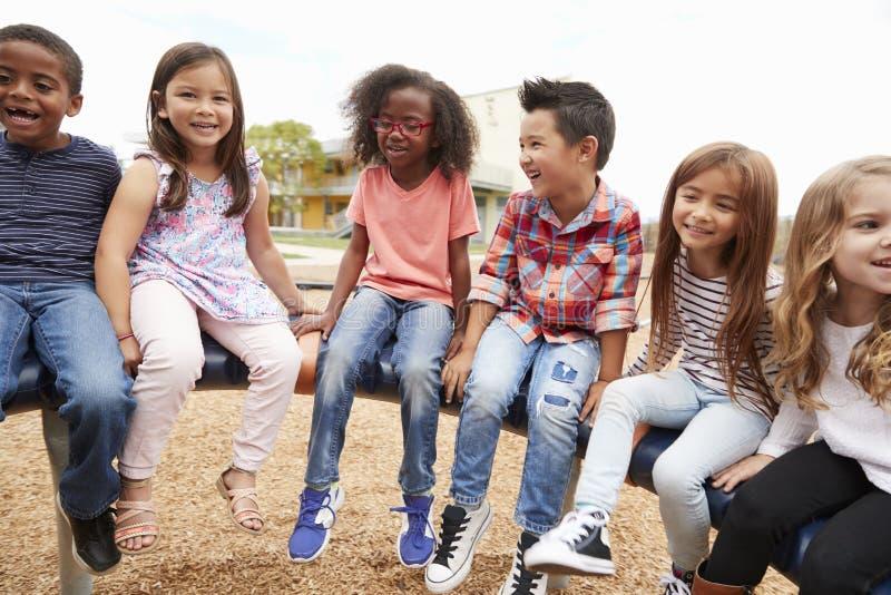 Grundskolavänner som sitter på en snurrkarusell royaltyfri fotografi