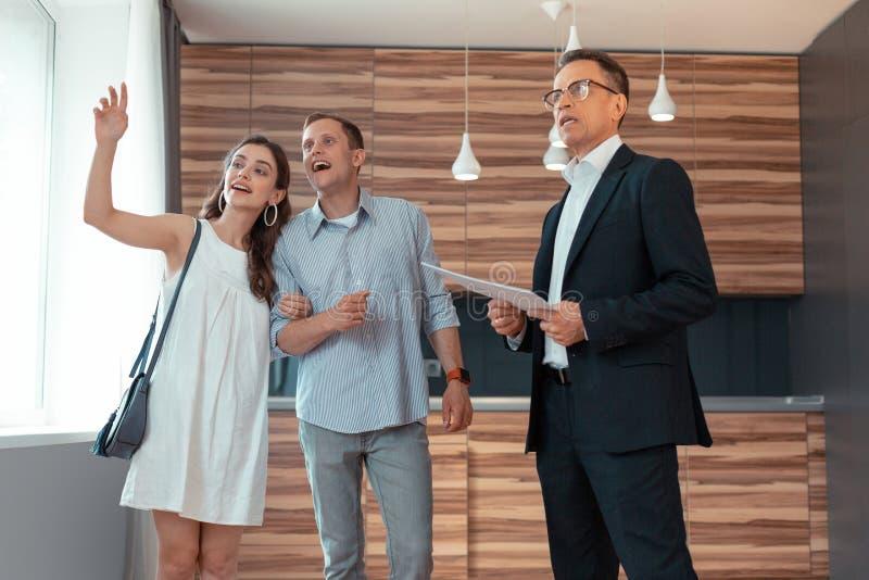 Grundstücksmakler, der über das Haus mit gerade verheiratetem Paar spricht stockfotos