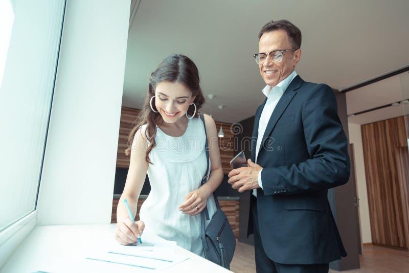 Grundstücksmakler, der den Kunden aufpasst, die Papiere zu unterzeichnen, nachdem Haus gekauft worden ist lizenzfreie stockfotos
