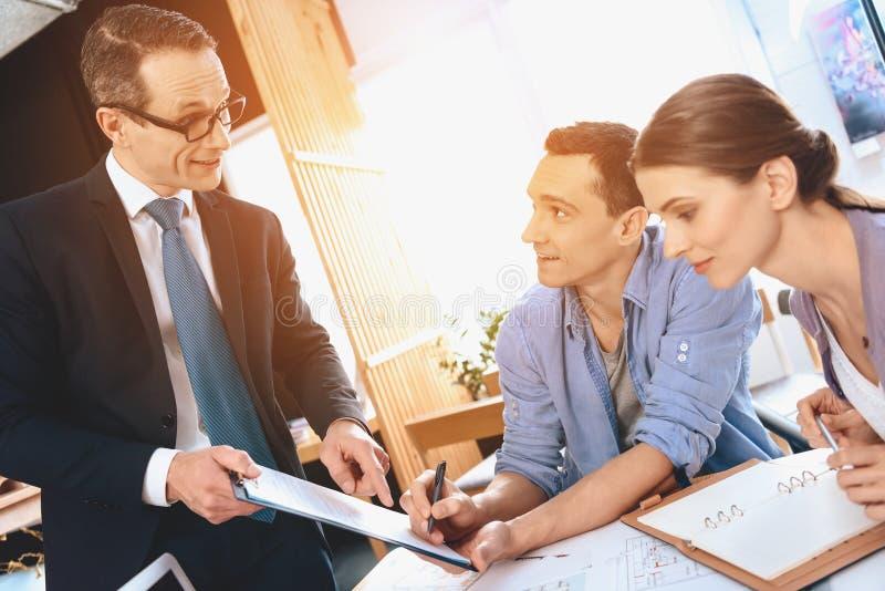 Grundstücksmakler, der am Schreibtisch im Büro sitzt Vater unterzeichnet Dokument für neue Wohnung lizenzfreies stockbild