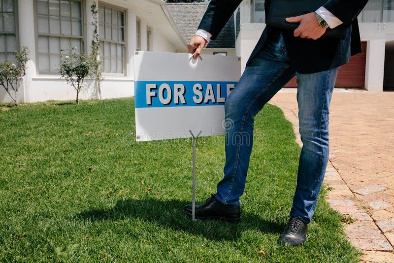 Grundstücksmakler mit a für Verkaufszeichenbrett außerhalb eines Hauses lizenzfreies stockfoto
