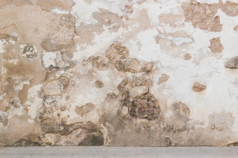 Grunge墙壁背景 老砖和石墙有明亮的被放弃的膏药的 库存照片