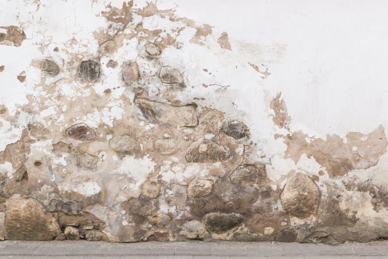 Grunge墙壁背景 老砖和石墙有明亮的被放弃的膏药的 免版税库存图片