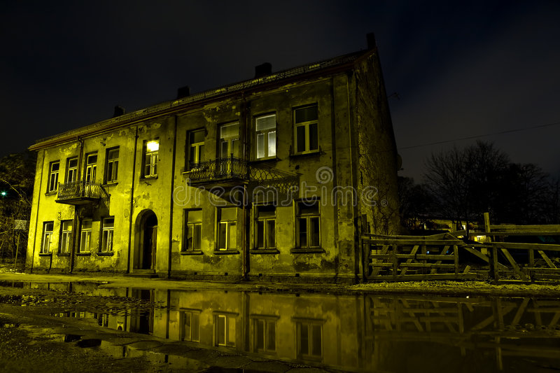 Grunge. View of shabby building reflecting in water. Grunge background. Old construction. Night shot stock image