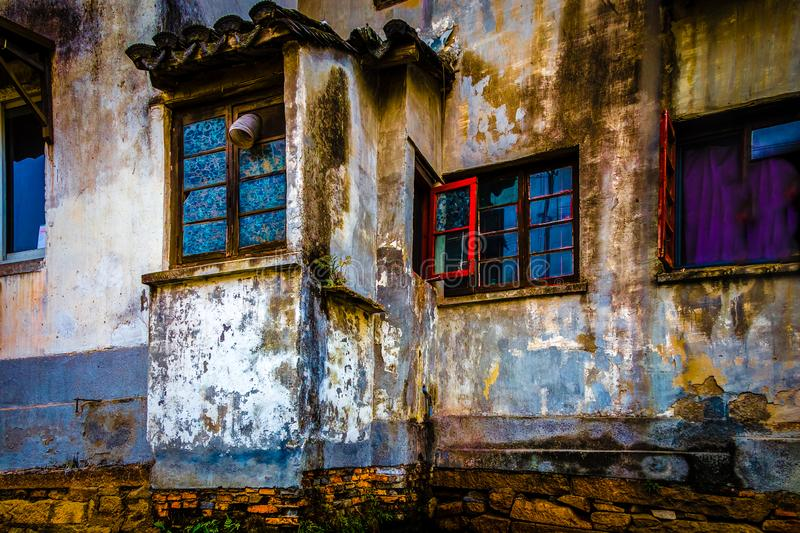 Grunge abandoned house Suzhou, China. Exterior of grunge abandoned home with blue windows along Grand Canal in Suzhou, China royalty free stock images