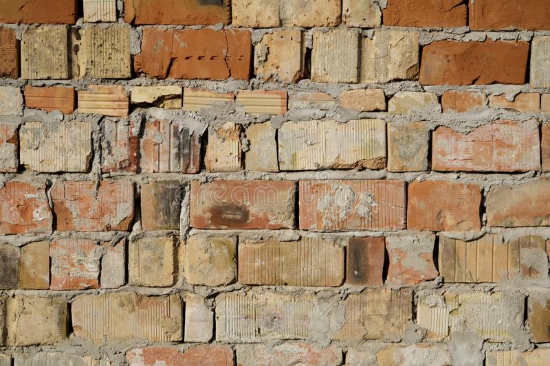 Grunge aged weathered cracked brick wall surface texture in good lights stock images