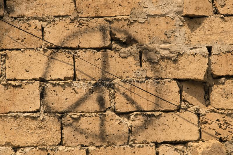 Grunge background of rustic bricks with sloppy mortar with spray painted peace sign and an electric wire running diagonally royalty free stock images