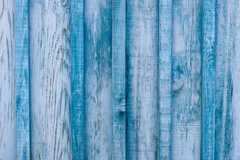 Grunge background. Wooden old blue fence. The gaps between the boards are clogged with slats. The paint is peeling and cracked stock photography