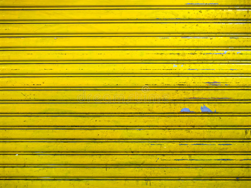 Grunge bright yellow roller shutter door texture background royalty free stock images