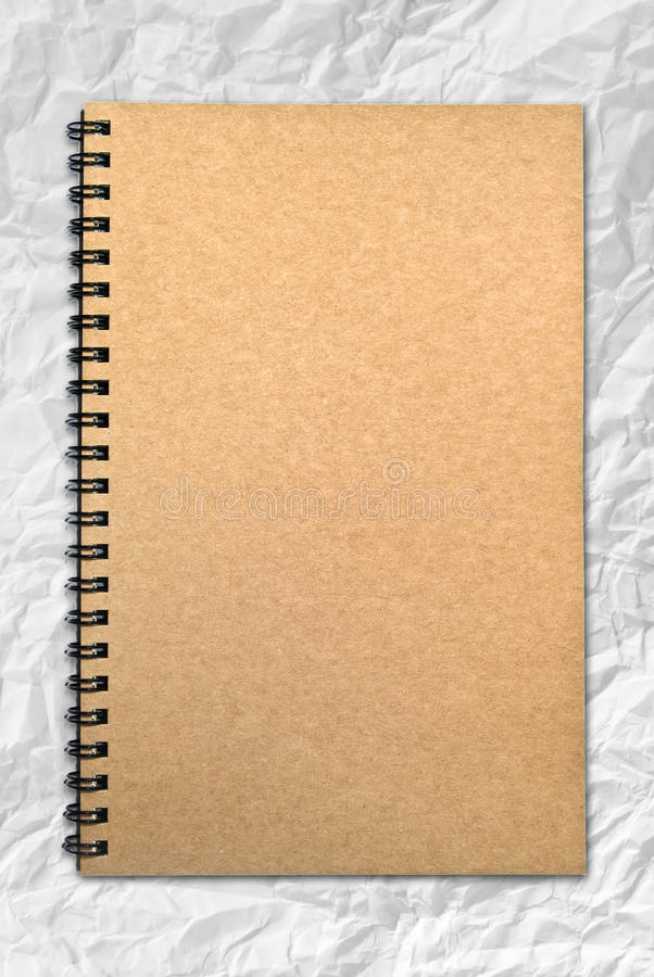 Grunge brown cover notebook on wrinkled paper stock image